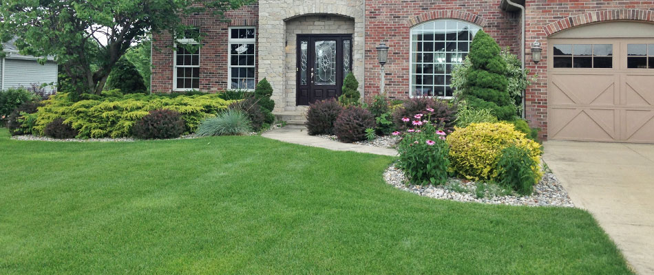 Rock landscape bed with mulch and red shrubs in Elkhart, IN.