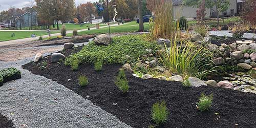 Home yard with custom landscape bed and rock mulch in Elkhart, IN.