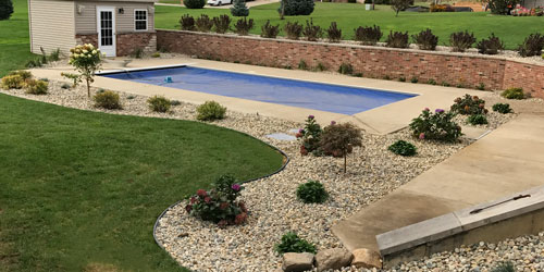 Home yard with custom landscape bed and rock mulch in Granger, IN.